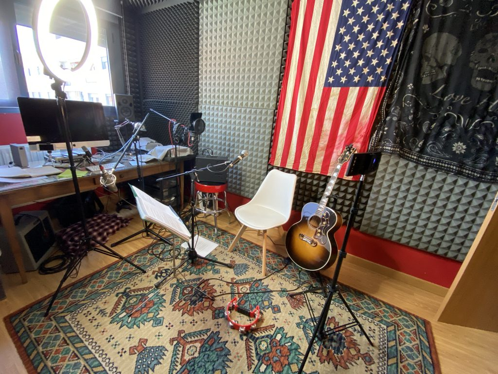 Foto de estudio de grabación de Alejandro Saguar dedicado a la grabación de video, con alfombra, aro de luz, y bandera de Estados Unidos en la pared. Junto a guitarra acústica y ordenador Mac de fondo