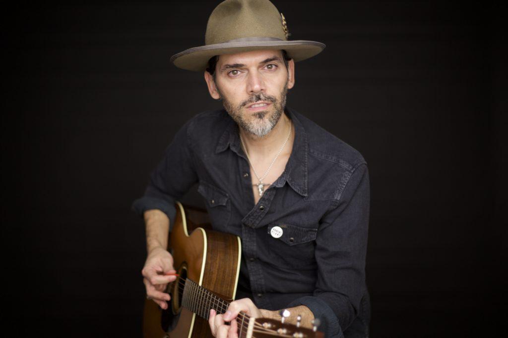Foto de estudio de Alejandro Saguar de frente, sentado medio cuerpo con guitarra acústica en las manos y sombrero country. Vestido con camisa negra marca Lee
